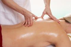 Woman having back massage. In studio stock photography