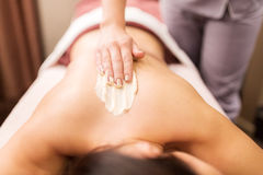 Woman having back massage with cream at spa. People, beauty, healthy lifestyle and relaxation concept - beautiful young woman lying and having back massage with Stock Images