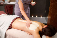 Woman having back massage with cream at spa. People, beauty, healthy lifestyle and relaxation concept - beautiful young woman lying and having back massage with Royalty Free Stock Photo