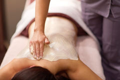 Woman having back massage with cream at spa. People, beauty, healthy lifestyle and relaxation concept - beautiful young woman lying and having back massage with Stock Image