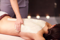 Woman having back massage with cream at spa. People, beauty, healthy lifestyle and relaxation concept - beautiful young woman lying and having back massage with Stock Photo