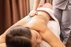 Woman having back massage with gel at spa. People, beauty, healthy lifestyle and relaxation concept - beautiful young woman lying and having back massage with Stock Photo