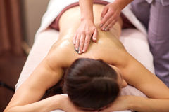 Woman having back massage with gel at spa. People, beauty, healthy lifestyle and relaxation concept - beautiful young woman lying and having back massage with Stock Photography