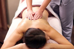 Woman having back massage with gel at spa. People, beauty, healthy lifestyle and relaxation concept - beautiful young woman lying and having back massage with Stock Images