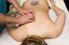 Woman having back massage from masseur Stock Image