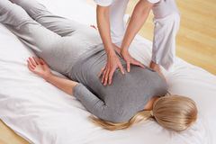 Woman having back massage from a professional. On a exercise mat on the floor royalty free stock photo