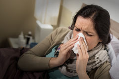 Woman having bad cold blowing her nose. Caucasian woman having bad cold blowing her nose Royalty Free Stock Image