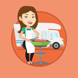 Woman having barbecue in front of camper van. Stock Photos