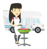 Woman having barbecue in front of camper van. Stock Photo