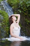 Woman having a bath in a waterfall Stock Photography