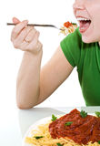 Woman having a bite of pasta Royalty Free Stock Images