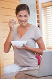 Woman having a bowl of cereals next to her laptop Royalty Free Stock Images