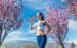Woman having break from running drinking water Royalty Free Stock Image