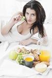 Woman having breakfast on bed Stock Photo