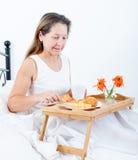 Woman having breakfast in bed Stock Photos