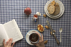 Woman having breakfast, her hands and a book Royalty Free Stock Images
