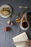 Woman having breakfast, her hands and a book Stock Images