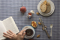 Woman having breakfast, his hands and a book Stock Photo