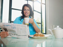 Woman having breakfast at home stock images