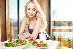 Woman having breakfast in kitchen Royalty Free Stock Photo