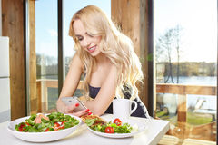 Woman having breakfast in kitchen Stock Image