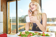 Woman having breakfast in kitchen Stock Photography