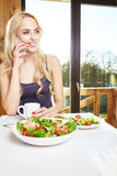 Woman having breakfast in kitchen Stock Photo