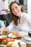 Woman having breakfast at kitchen table, smiling, portrait, man standing in background Royalty Free Stock Photo
