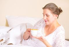 Woman having breakfast, relaxing in hotel bed Royalty Free Stock Photo