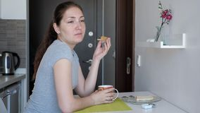 Woman is having a breakfast, sandwitch and cup of tea in small kitchen on rented apartments at vacation. stock video