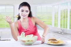Woman Having Choice Between Burger And Salad Stock Photos