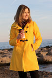 Woman having coffee at the beach. Young woman in yellow wool jacket holding a coffee cup standing on the beach Stock Images