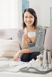 Woman having a coffee break. Happy woman at home having a relaxing coffee break and reading a magazine Royalty Free Stock Photo