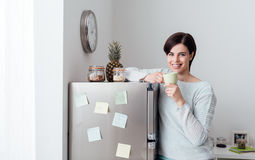 Woman having a coffee break at home. Young woman having a coffee break at home, she is leaning on the fridge and smiling at camera royalty free stock image