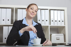 Woman having coffee break in office. Friendly smiling bank clerk having a break using her tablet computer on the desk while drinking a cup of coffee cappuccino Royalty Free Stock Photography