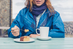 Woman having coffee and cake at table outside Royalty Free Stock Photos