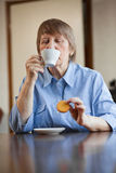 Woman having coffee and cookie Royalty Free Stock Images