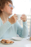Woman having coffee with cookies Royalty Free Stock Photos