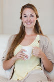 Woman having coffee on her sofa Royalty Free Stock Photography