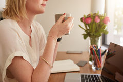 Woman having coffee at her work desk Stock Photos
