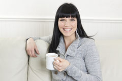 Woman having a coffee and relaxing at home Stock Photography
