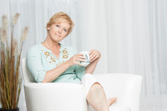 Woman having coffee while relaxing at home Stock Image