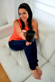 Woman having coffee sitting on sofa Royalty Free Stock Photos