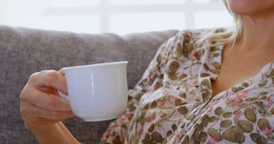 Woman having coffee on sofa at home 4k stock video