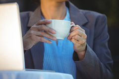 Woman having coffee using her laptop Royalty Free Stock Photography