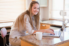 Woman having coffee while using a laptop Royalty Free Stock Photos