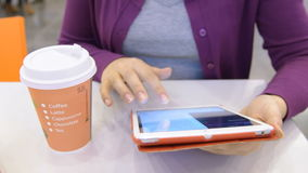 Woman having coffee and using tablet computer. Woman drinking coffee and typing on digital tablet in the cafe stock video footage