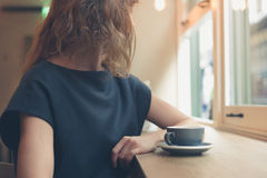 Woman having coffee by window in cafe Royalty Free Stock Image