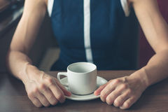 Woman having coffee by the window in a diner. A young woman is having a cup of coffee by the window in a diner Royalty Free Stock Image