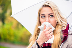 Woman having cold or flu due to bad autumn weather Royalty Free Stock Photography